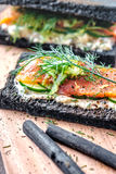Charcoal Bread Smoked Salmon Sandwiches on wood board Royalty Free Stock Photo