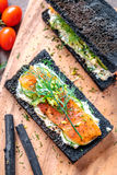 Charcoal Bread Smoked Salmon Sandwiches on wood board stock photo