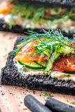 Charcoal Bread Smoked Salmon Sandwiches on wood board stock photos
