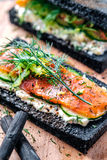 Charcoal Bread Smoked Salmon Sandwiches on wood board stock images