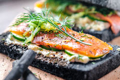 Charcoal Bread Smoked Salmon Sandwiches on wood board royalty free stock photography