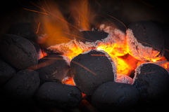 Charcoal briquettes with fire sparks. Charcoal briquettes ready for barbecue grill.Black vignette royalty free stock photography