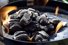 Charcoal briquettes with flames. Close up view of charcoal briquettes in small barbecue with flames and ash Royalty Free Stock Photography