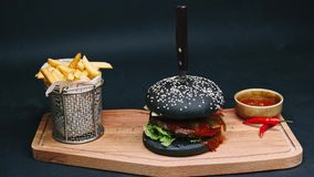 Charcoal burger with french fries and red sauce are on the board, pierced with a knife, and ready to eat in 4k stock footage