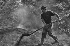 Charcoal burner. Charcoal - burner working heat and smoke - monochrome. Photo taken in Harghita county, Romania on May 30th, 2015 stock photo