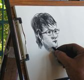 Charcoal drawing. Artist drawing a man with eye glasses on white paper Royalty Free Stock Image