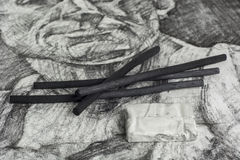 Charcoal drawing and sticks. Charcoal sticks with drawing on the background Royalty Free Stock Photos
