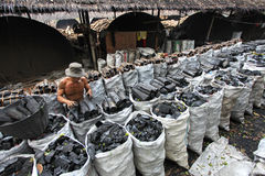 Charcoal factory. NAKHON SI THAMMARAT, THAILAND - MAY 12 : Unidentified worker in a charcoal factory packs charcoals into plastic bags for shipment on May 12 Royalty Free Stock Photos