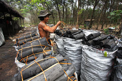 Charcoal factory worker. NAKHON SI THAMMARAT, THAILAND - MAY 12 : Unidentified worker in a charcoal factory packs charcoals into plastic bags for shipment on May Royalty Free Stock Images
