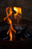 Charcoal flame and ember. An iron bucket full of charcoal dark with some flames ember and ash Stock Photography