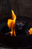 Charcoal flame and ember. An iron bucket full of charcoal dark with some flames ember and ash Stock Image