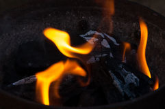 Charcoal flame and ember. An iron bucket full of charcoal dark with some flames ember and ash Royalty Free Stock Image