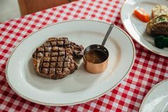 Charcoal grilled wagyu Ribeye steak served with BBQ sauce and baked potato in white plate on red and white pattern tablecloth Stock Photo