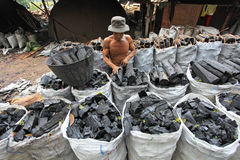 Charcoal production. NAKHON SI THAMMARAT, THAILAND - MAY 12 : Unidentified worker in a charcoal factory packs charcoals into plastic bags for shipment on May 12 Royalty Free Stock Photography