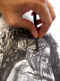 Charcoal Sketch 1. A hand using a charcoal stick to sketch a female figure. The sketch is of the photographer's original artwork royalty free illustration