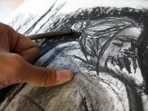 Charcoal Sketch 2. A thumb smudging the charcoal on the sketch pad. The sketch is of the photographer's original artwork stock illustration