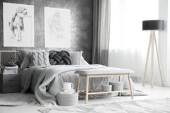 Charcoal sketches on concrete wall. Charcoal sketches hanging on a concrete wall near the window in bright bedroom interior with wooden lamp and bench in front stock image