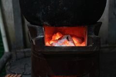 The charcoals wood are burned with fire in the vintage stove when cooking some food in black pot royalty free stock photos