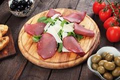 Charcuterie board. With italian bresaola cured beef, grana padano cheese and rocket salad Royalty Free Stock Photo