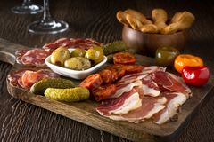 Charcuterie Board Platter. A delicious charcuterie assortment of meat, olives, gherkins, and pickled peppers with breadsticks on a wooden background Stock Image