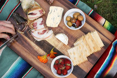 Charcuterie Board. With prosciutto, duck breast, salami, olives, cheese, crackers, and strawberries.  Picnic blanket and grass in background Stock Image