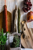 Charcuterie, variety of sausages hanging on hook, wood cutting board, string with dry peppers, fresh garden herbs, Provence Royalty Free Stock Images