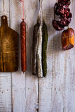 Charcuterie, variety of sausages hanging on hook, wood cutting board, string with dry peppers nyora, Spanish meat delicacies Royalty Free Stock Photo