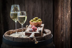 Chardonnay wine with olives and cold cuts on old barrel Royalty Free Stock Image