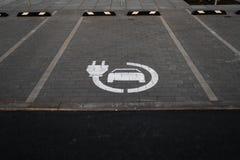 Charge libre de voiture électrique - parkings vides pendant le coucher du soleil d'or d'heure à un centre commercial typique popu photos stock