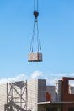 Charge lourde accrochant sur le chantier de construction de l'immeuble de brique Photos libres de droits