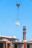 Charge lourde accrochant sur le chantier de construction de l'immeuble de brique Image stock