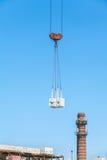 Charge lourde accrochant sur le chantier de construction de l'immeuble de brique Images stock