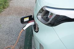 Charged electric car. Electric Car Being Charged. Charging an electric car with the power supply plugged in royalty free stock photo