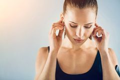 Pensive sporty brunette listening to music. Charged with motivation. Beautiful focused young fitness woman putting earphones in her ears and enjoying the music Stock Images