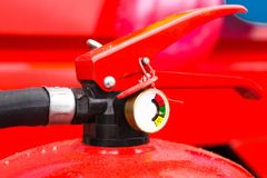 Charged and ready to use fire extinguisher with a manometer. Close-up op a part of a fire extinguisher. The top part of the red powder fire extinguisher royalty free stock images