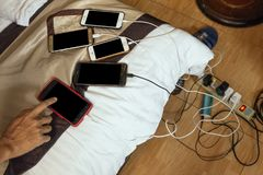 Charged smart phones with right hand pointed on bed with charge cords in a mess at hotel room in Hanoi, Vietnam.  Stock Images