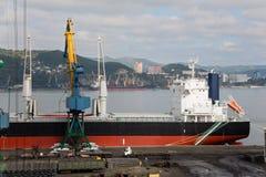 Chargement de métal roulé au port de Nakhodka, Russie Photographie stock libre de droits