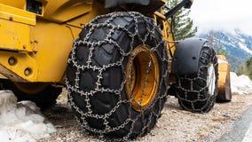 Chargeur avant pour le déblaiement de neige avec des chaînes de neige en métal sur des roues Déblaiement de neige dans les montag photos libres de droits