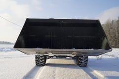 Chargeur avec un seau énorme se tenant sur la route neigeuse Image libre de droits