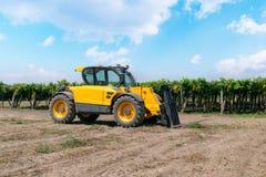 Chargeur de chariot élévateur de couleur jaune dans un domaine sur un fond de vignoble photographie stock libre de droits
