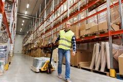 Chargeur de transport d'homme avec des marchandises à l'entrepôt Photo stock