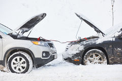 Charging automobile discharged battery by booster jumper cables at winter Royalty Free Stock Image