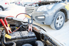 Charging automobile discharged battery by booster jumper cables at winter Royalty Free Stock Images
