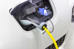 The charging the battery for the car new Automotive Innovations. The power supply plugged into an electric car being charged, concept of energy innovation stock photography