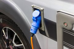 The charging the battery for the car new Automotive Innovations. The power supply plugged into an electric car being charged, concept of energy innovation royalty free stock photo