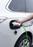 Charging battery of an electric car. Charging battery of an electric white car Stock Photography