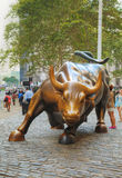 Charging Bull sculpture in New York City. NEW YORK CITY - September 3: Charging Bull sculpture with people on September 3, 2015 in New York City. The sculpture Royalty Free Stock Photo