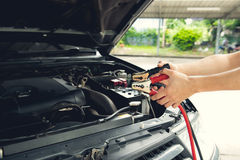 Charging car battery with electricity trough  jumper cables Royalty Free Stock Photography