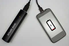 Charging cellphone battery with power bank. Technology concept Royalty Free Stock Images