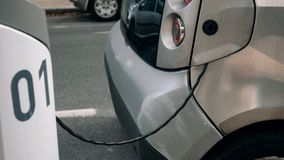 Charging cord from a car. Detail - an electrocar with a charging cord, connecting it to a charger royalty free stock photo